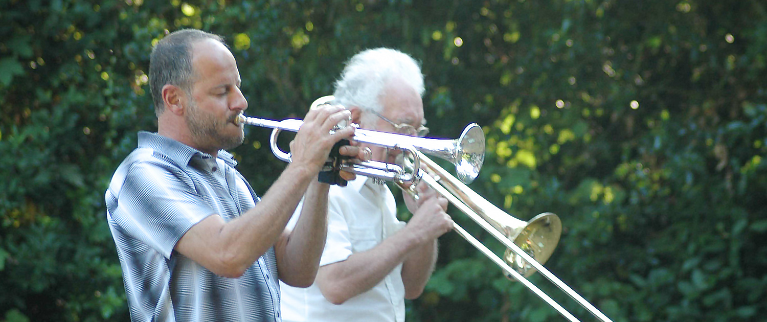 Photo of two musicians playing trombones at an event at Cornelius House Residential Care Home