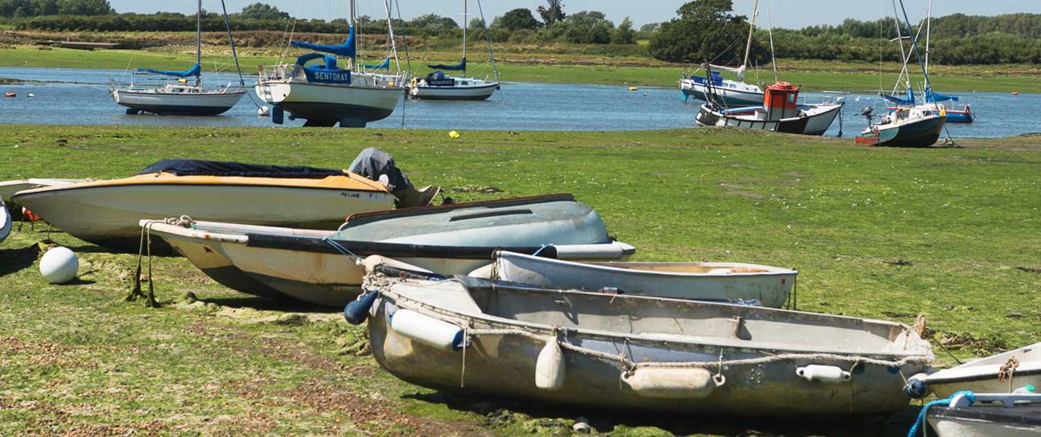 A photo of boats at Bosham Harbour with the tide out